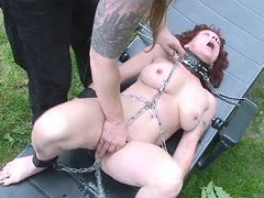 Redheaded German babe is chained and fingered outdoors