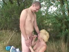 Blonde granny fucks young guys on the field